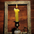 Old candle on table on wooden background — Stock Photo