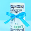 Dollars with gift bow on blue background — Stock Photo