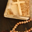 Bible, rosary and cross on wooden table close-up — Stok fotoğraf