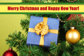 Regalo en el árbol de navidad sobre fondo verde — Foto de Stock