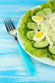 Deliziosa insalata con uova, cavoli e cetrioli sul tavolo blu — Foto Stock