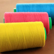 Stock Photo: Colored bobbins on brown background