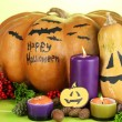 Composition for Halloween with pumpkins and candles on wooden table on color background — Stock Photo