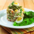 Russian traditional salad Olivier, on color napkin, on wooden background — Stock Photo #33198333