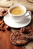 Cup of tasty coffee with tasty cookies, on wooden background — Stock Photo