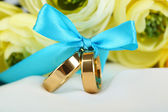 Wedding rings tied with ribbon on white fabric — Stock Photo