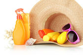 Bottles with suntan cream and sunglasses in hat isolated on white — Stock Photo