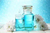 Glass bottles with color essence, on wooden table, on blue background — Stock Photo