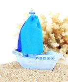 Blaue spielzeug schiff auf sand isoliert auf weiss — Stockfoto