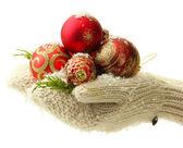 Mujer las manos en guantes de bolas de árbol de navidad, sobre fondo de color — Foto de Stock
