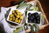 Olives dans des bols avec branche sur la serviette dans le panier sur la table en bois — Photo