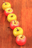 Small apples on wooden background — Stock Photo