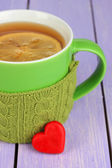 Cup with knitted thing on it on wooden table close up — Stock Photo