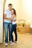 Young couple with keys to your new home on room background — Stok fotoğraf