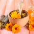 Medicine bottles and calendula flowers on wooden background — Stock Photo #33314401