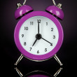 Purple alarm clock on dark purple background — Stok fotoğraf