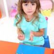 Little girl molds from plasticine sitting at table in room on shelves background — Stock Photo