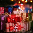 Many gifts and glasses of champagne on bright background — Stock Photo