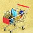 Christmas gifts in shopping trolley, on golden shiny background — Stock Photo