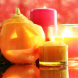 Composition for Halloween with pumpkin and candles on red background — Stock Photo