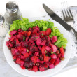 Beet salad on plate on napkin on wooden board isolated on white — Stock Photo