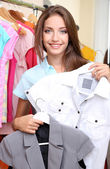 Beautiful girl chooses clothes on room background — Stock Photo