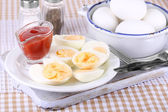 Boiled eggs on wooden board on tablecloth — Stock Photo