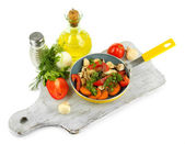 Sliced fresh vegetables in pan on wooden board isolated on white — Stock Photo