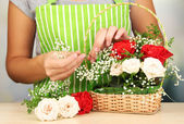 Florist makes flowers bouquet in wicker basket — Stockfoto