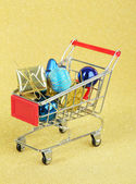 Christmas gifts in shopping trolley, on golden shiny background — Zdjęcie stockowe