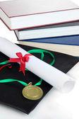 Médaille pour les réalisations en matière d'éducation avec diplôme, chapeau et livres bouchent — Photo