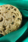 Beautiful Christmas ball on green satin cloth — Stock Photo