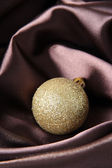 Beautiful Christmas ball on brown satin cloth — Stock Photo