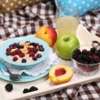 Oatmeal in plate with berries on napkins on wooden tray on bad — Stock Photo #33377435