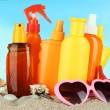 Bottles with suntan cream and sunglasses, on blue background — Stockfoto
