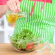 Happy smiling woman in kitchen preparing vegetable salad — Stock Photo