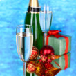 Bottle of champagne with glasses and Christmas balls on blue background — Stock Photo
