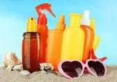 Lahve s opalovací krém a sluneční brýle, na modrém pozadí — Stock fotografie