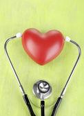 听诊器和木制表特写的心 — 图库照片