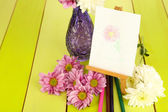 Flowers and small easel with picture — Stock Photo