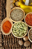 Many different spices and fragrant herbs on braided table close-up — Stock fotografie