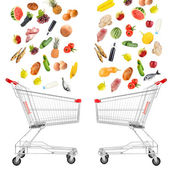 Food products falling in shopping cart isolated on white — Stock Photo