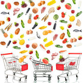 Food products flying out around shopping carts isolated on white — Stock Photo