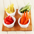 Bright fresh vegetables cut up slices in bowls on wooden table close-up — Stock Photo #33450755