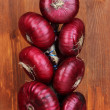 Fresh red onions on wooden background — Stock Photo