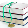 Medal for achievement in education with books isolated on white — Stock Photo
