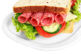 Tasty sandwich with salami sausage and vegetables on white plate, isolated on white — Stock Photo