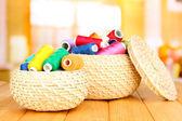 Cestas de vime com acessórios para bordado na mesa de madeira, no fundo brilhante — Foto Stock
