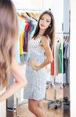 美丽女孩试图靠近房间背景上的镜像的衣服 — 图库照片