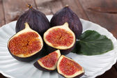 Ripe figs on plate wooden table close-up — Stock Photo